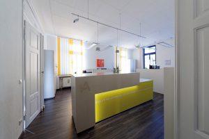Empfangsbereich Tresen hell Beton und Glas farbig