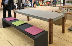 Betontischplatte mit Holzbeinen und Betonbank dunkel auf Garten Ausstellung