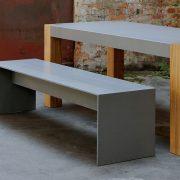 Sitzbank aus Beton mit Betontischplatte mit Tischbeinen aus Holz