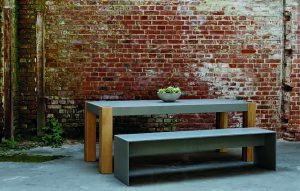 Tisch aus Beton mit Tischbein Holz hinter Betonbank