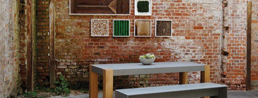 Tisch Beton mit Eiche Beinen hinter Betonbank leicht Wallapp an Zieglsteinwand