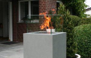 Betonsäule mit Feuer in Windschutz