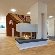 Raumteiler Kamin mit Kaminhaube aus Beton und Kaminbank