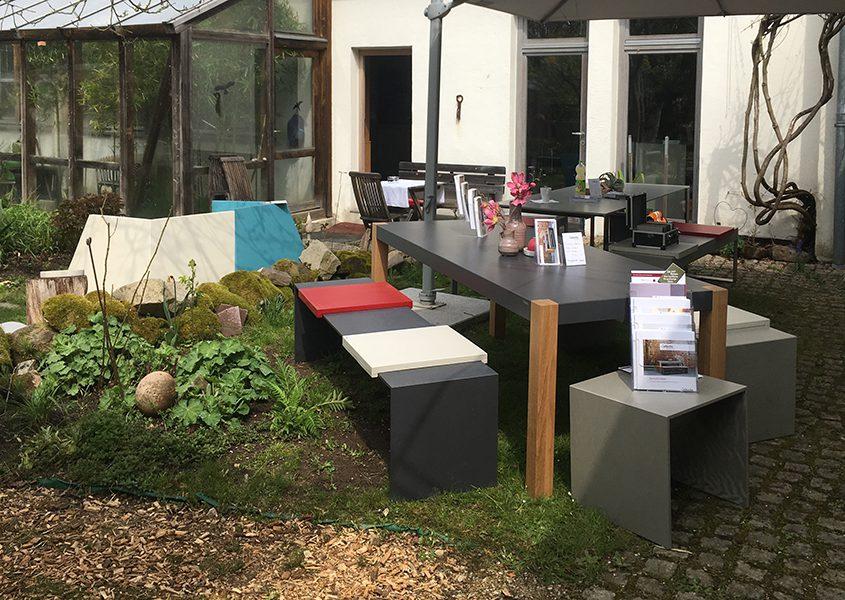 Gartenterrasse mit Betontisch mit Holzfüßen und schlanker Betonbank und Betonhocker