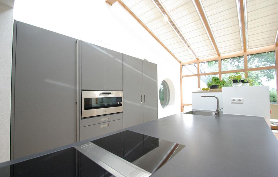moderne graue Kueche mit Arbeitsflaeche Kochinsel aus Beton