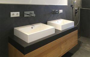 Beton-Waschtischplatte vor dunkler Wandverkleidung