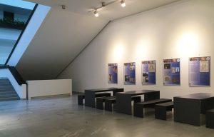 Uni Würzburg Kantine - dunkle Betontische und Betonbänke aus filigranen Betonplatten unter Treppe